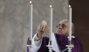 Pope Francis elevates the Eucharist during Ash Wednesday Mass at the Basilica of Santa Sabina in Rome Feb. 18. (CNS photo/Paul Haring) See POPE-ASHES Feb. 18, 2015.
