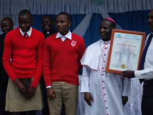 Students and a patron of Nyakasura School pose with the Bishop after awarding them the certificate. This was the school with the best student in Fine Art.