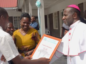 The Bishop awarding a certificate to one of the best school.